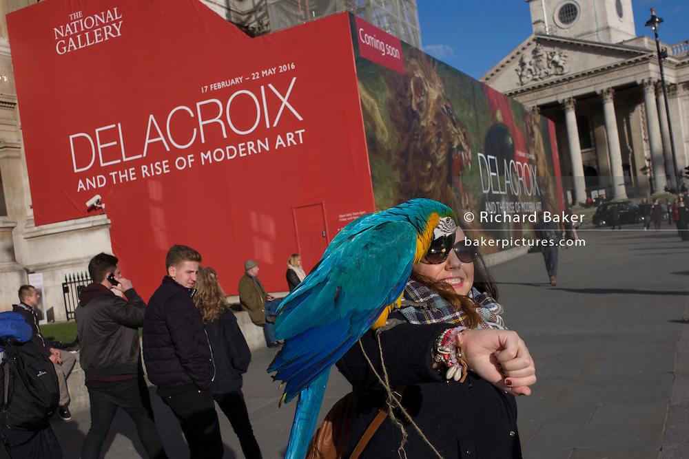 A woman holds a parrot in front of the broad message on a hoarding announcing the next major exhibition by Delacroix at the National Gallery in London,