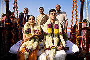 At a Hindu wedding, the bride, Shweta Singhal and groom, Rohit clasp each others hands as they  sit on a swing and take part in a ritual known as oonjal, in which the forces of good are propitiated to keep the couple safe from evil thoughts and curses, they are surrounded by family and close friends, Neemrana Fort Palace, Rajasthan, India.
