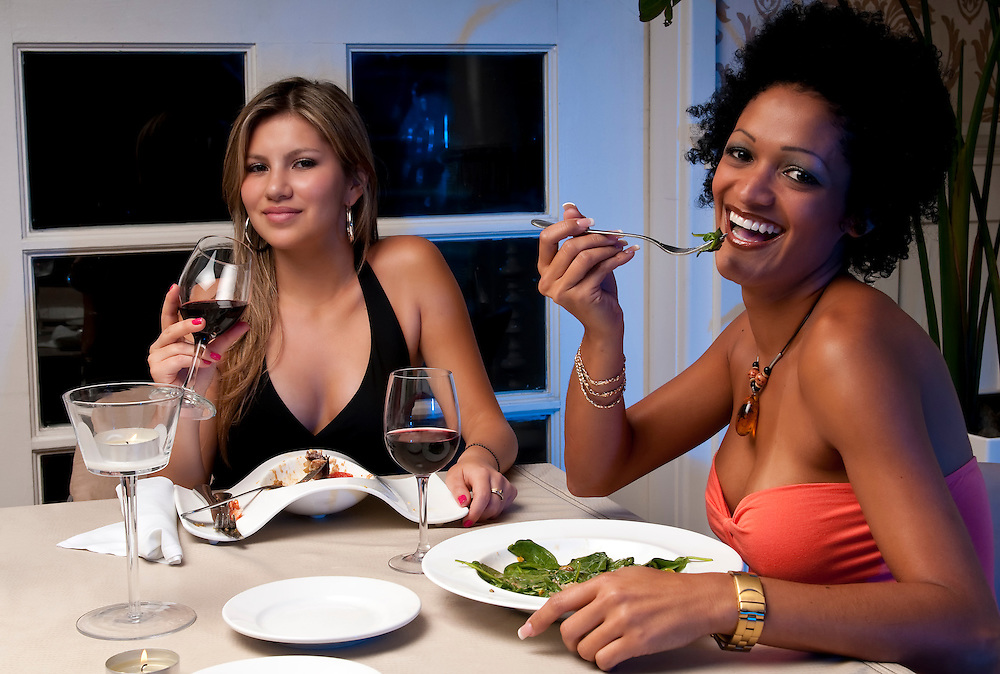 2 Young girls having dinner in a restaurant.