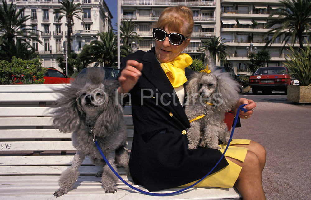 An stylish elderly lady sits on a public bench with her two pet poodles, on 10th May 1996, in Monaco, Monte Carlo.