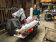 03 AUGUST 2016 - BANGKOK, THAILAND: A man who lives in the Pom Mahakan slum and sells noodles from his pushcart leaves his home for work. Residents of the slum have been told they must leave the fort and that their community will be torn down. The community is known for fireworks, fighting cocks and bird cages. Mahakan Fort was built in 1783 during the reign of Siamese King Rama I. It was one of 14 fortresses designed to protect Bangkok from foreign invaders. Only of two are remaining, the others have been torn down. A community developed in the fort when people started building houses and moving into it during the reign of King Rama V (1868-1910). The land was expropriated by Bangkok city government in 1992, but the people living in the fort refused to move. In 2004 courts ruled against the residents and said the city could take the land. Eviction notices have been posted in the community and people given until April 30 to leave, but most residents have refused to move. Residents think Bangkok city officials will start evictions around August 15, but there has not been any official word from the city.      PHOTO BY JACK KURTZ