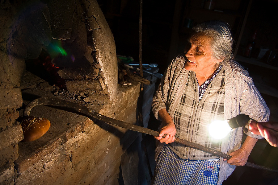 """An elderly woman bakes bread in a traditional bread oven in Santa Catarina Lachatao, part of the Pueblos Mancomunados, a network Zapotec villages in the Sierra Norte Mountains of Oaxaca state, Mexico on July 16, 2008. The Pueblos Mancomunados, literally """"joint villages"""", welcome low-impact tourism with cabins, home stays and a large network of signposted trails and forest roads throughout the spectacular landscape which the communities share."""