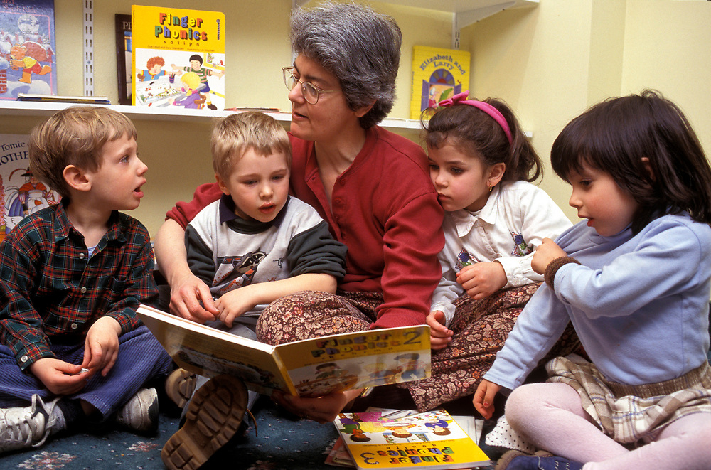 Primary school teacher sitting on the floor reading to a group of children,
