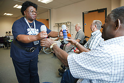 Giving out weights at exercise class for wheelchair users at Day Centre.