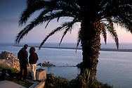 Couple looking out over Pacific Ocean at sunset, from Inspiration Point overlook, Corona del Mar, Newport Beach, California