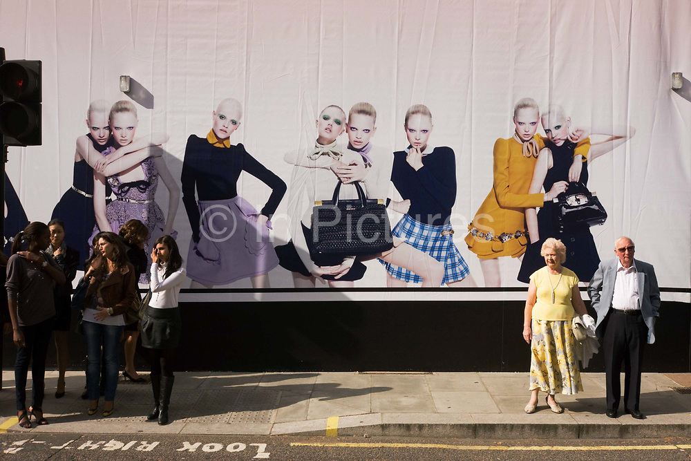 Young women on a shop hoarding with pedestrians and an elderly couple about to cross Brutoin Street in central London. An image of young and older generations is seen at this busy crossing where young women stand to one side, out for a shopping trip along the fashionable and expensive Bond Street. To their left is an elderly couple who stand separated by a wide distance from the girls - a metaphor for the wide generation gap in Britain today. The young girls live in an age of materialism and wealth while the people from their grandparents' era have survived unanticipated hardship, war and technological changes. In the background are the faces and poses of fashion models whose androgynous looks are as different to the elderly as the females along the street.