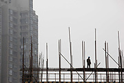 Construction workers operate on a building site scaffolding in Shanghai, China on 06 March, 2009.  For the past decade, Shanghai has underwent the largest reconstruction in recorded history, over 20 million square meters of land, approximately a third of Manhattan, were developed between year 200 and 2005 alone.