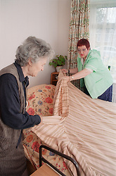 Elderly woman and carer making bed,