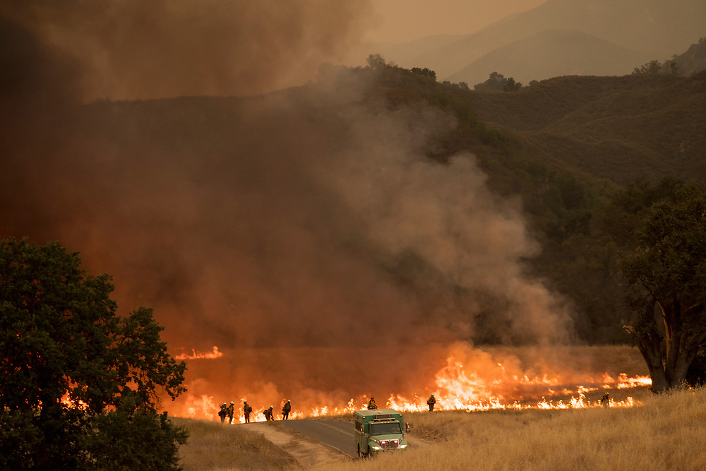 Firefighters light a controlled burn along Nacimiento-Fergusson Road to help fight the Dolan Fire near Jolon, Calif. on Sept. 9, 2020.