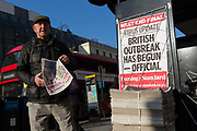 On the day that the UK Governments Chief Scientific Advisor, Sir Patrick Vallance said that the Coronavirus Covid-19 outbreak was now spreading person to person in the UK, a Londoner picks up copies of the capitals London Evening Standard newspaper outside Charing Cross railway station, on 6th March 2020, in London, England.