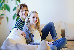 Grandmother and granddaughter relaxing on couch, smiling, portrait
