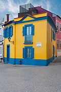 Traditional house facade in yellow stucco and blue paint in Aveiro, Portugal