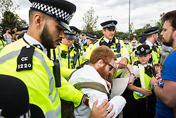 London, UK. 2 September, 2019. Police officers remove activists from the road outside ExCel London on the first day of week-long protests against DSEI 2019, the world's largest arms fair. The first day of creative action was hosted by activists calling for a ban on arms exports to Israel and featured workshops, speakers, street theatre and dance. Israeli arms companies display weapons at DSEI marketed as 'combat-proven' following deployment against Palestinian communities.