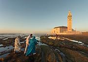 People walking along rocky coast near Hassan II Mosque at foggy sunset. Casablanca, Morocco