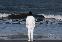 Glasgow-based Iranian artist Iman Tajik brought his performance art piece to Portobello beach this weekend. The piece, entitled 'Where the Body Meets The Land',  involved Iman spending four hours walking up and down the sand. As he paced from a flag pole, buried in the sand, hoisting up a shimmering gold emergency blanket, to the seashore and back he created a line in the sand. This act of line making refers to the thousands of refugees and migrants that have disembarked, including those that did not survive, onto UK shores. Pictured: Iman Tajik<br /> © Jon Davey/ EEm