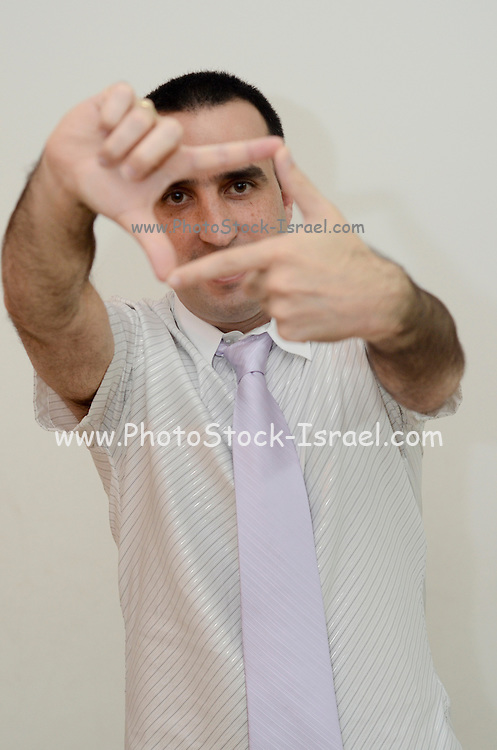 Young Man in his thirties with button down shirt and tie Uses his fingers to frame a picture