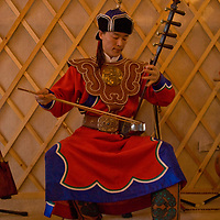 A young Mongolian musician plays a traditional fiddle in his home in Ulaanbaatar, which he and his father have decorated to look like a ger (yurt).