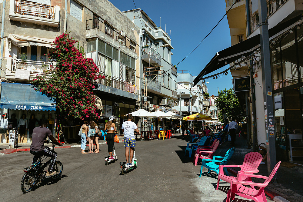 People and electric scooter riders, are seen enjoying a hot summer afternoon at Levinsky Street, a pedestrian zone in the Levinsky Market area in southern Tel Aviv, Israel, on August 19, 2020. A ban on vehicles in Levinsky Street was started at the end of 2019, as a pilot of a new municipality initiative to reduce the number of private cars in the inner city. The Tel Aviv-Jaffa  Municipality is planning to convert 11 popular streets in the city, into pedestrian zones shut to vehicles in the coming months.