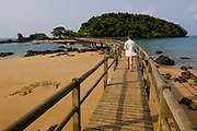A tourist walks at Bom Bom resort, in Príncipe island,. Bom Bom Resort is one of the most exclusive resorts in Africa.It is very famous for its Big Game fishing. The main bungalow area is connected to the restaurant by a bridge. The restaurant is in Bom Bom isle.