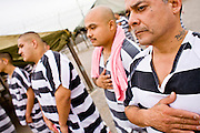 """17 JULY 2006 - PHOENIX, AZ: Inmates WILLIE ZAMORA (RIGHT), ARTHUR HERNANDEZ and others stand with their hands over the hearts while the National Anthem is played in """"Tent City"""" in the Maricopa County Jail in Phoenix, AZ. There are about 650 inmates living in the tents. Maricopa County Sheriff Joe Arpaio recently started playing the Star Spangled Banner and God Bless America twice a day in the county jails. Inmates are encouraged, but not forced, to stand at attention with their hands over their hearts, when the music is played. When asked about the new policy Arpaio said, """"Our men and women are fighting and dying for our country in Iraq and that's the least these inmates can do."""" In 2011, the US Department of Justice issued a report highly critical of the Maricopa County Sheriff's Department and the jails. The DOJ said the Sheriff's Dept. engages in widespread discrimination against Latinos during traffic stops and immigration enforcement, violates the rights of Spanish speaking prisoners in the jails and retaliates against the Sheriff's political opponents.      PHOTO BY JACK KURTZ"""