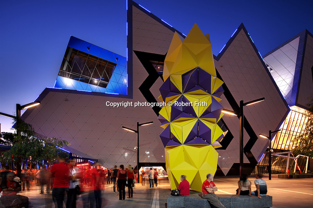 """Totem<br /> by Geoffrey Drake Brockman<br /> <br /> Totem is an interactive spatial robot. It has 108 reconfigurable petals and is able to react to pedestrian movement. Totem incorporates a laser projection artwork titled """"Translight"""" that projects nightly onto the Eastern wall of the Perth Arena. Totem / Translight is a permanent public art commission installed at the Perth Arena."""