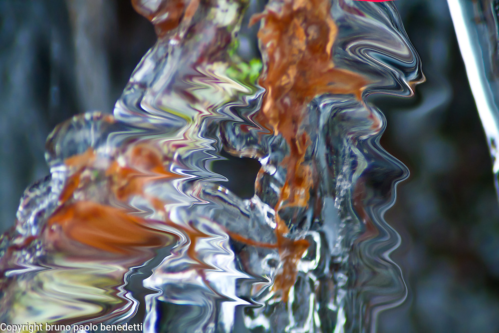 abstract ice reflections in winter. Brown color inside ice. Light filtering through a fluid ice shape makes colors bright and with many shades.