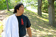 Asian man age 22 preparing to participate in dragon ceremonial dance. Dragon Festival Lake Phalen Park St Paul Minnesota USA