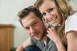 Portrait of couple in living room and smiling, Munich, Bavaria, Germany