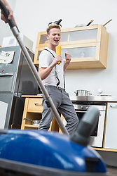 Young male gay couple having fun in kitchen