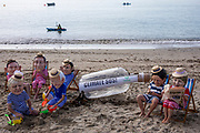 A giant message in a bottle has washed up on the beach from countries ravaged by climate change, but the G7 leaders are too busy relaxing in their swimming costumes in deckchairs to notice, Oxfam campaigners pose as G7 leaders on a beach on the 12th of June 2021 near Falmouth, Cornwall, United Kingdom. Oxfam is calling on the G7 countries to commit to cutting emissions further and faster and provide more finance to help the most vulnerable countries respond to the impacts of climate change.(photo by Andy Aitchison/Oxfam)
