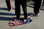 pvcHATEMONGERS2/9-21-06/ASEC.  Johnathan Phelps (CQ), center, of Topeka, KS, stands on an American Flag, next to his wife Shirley Phelps-Roper (CQ), left, and their son Hezekiah Phelps (CQ), age 15, photographed Thursday Sept. 21, 2006 in Rio Rancho, N.M..  These members of the Westboro Baptist Church were protesting outside Vista Verde Cemetery during the funeral of Spc. Alexander Jordan, who was killed Sept. 10 while serving in Iraq.  (Pat Vasquez-Cunningham/Journal)