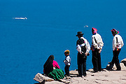Locals stand looking out over the dark blue water of Lake Titicaca and passing boats from an overlook on Amantani Island, Peru.