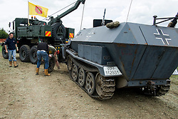 The damaged wheel with a solid rubber tyre is so heavy it requires three men to lift it from the ground onto the Halftracks bonnet before the vehicle can be towed out of the public arena<br /> <br /> 05 July 2015<br />  Image © Paul David Drabble <br />  www.pauldaviddrabble.co.uk