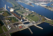 Nederland, Zeeuwsch-Vlaanderen, Terneuzen, 15/11/2001; sleepboten manoeuvreren zeeschip Kanin (uit een van de Baltische landen, geladen met erts / steenkolen) in de grote zeesluis in Terneuzen, begin Kanaal Terneuzen-Gent; kustvaart scheepvaart haven waterbouw steenkool erts, zie ook detailfoto. Scheepvaart. Sluizen.<br /> luchtfoto (toeslag), aerial photo (additional fee)<br /> photo/foto Siebe Swart
