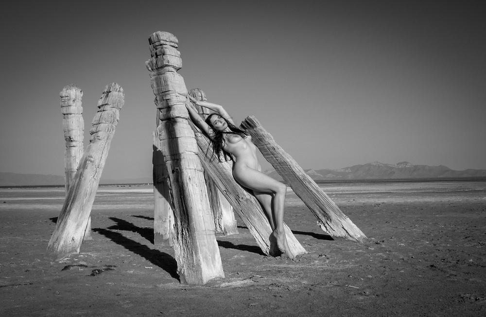 Photo of a nude woman standing against lake pilings in the Great Salt Lake, Utah