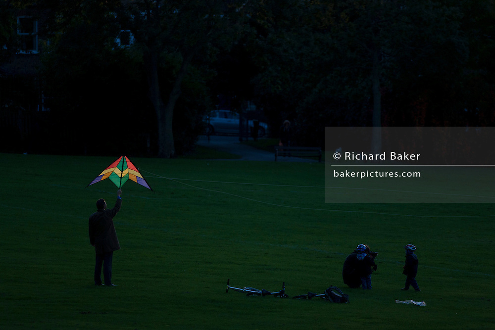 In late sunshine, a family of parents and two young children try to launch a stunt kite into the air in a south London park.