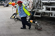 "During the turnround of the British Airways jet aircraft, a refueller drags the heavy fuel nozzle from his bowser truck on the apron at Heathrow Airport's Terminal 5. He is about to plug the connections into the airfield's underground reservoirs from where some 109 tons of Jet A1 aviation fuel flowing at a rate of 3,000 litres a minute will be uplifted into the wing tanks of a Boeing 747-300, a typical quantity of extra fuel for this aeroplane bound for Los Angeles. From writer Alain de Botton's book project ""A Week at the Airport: A Heathrow Diary"" (2009). ."