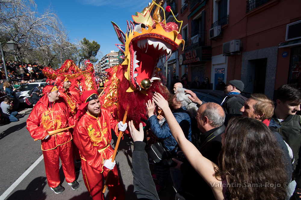 Madrid, Spain. 18th February, 2018. People touching a dragon in order to get good luck in the new year during the Chinese New Year parade in Madrid. © Valentin Sama-Rojo