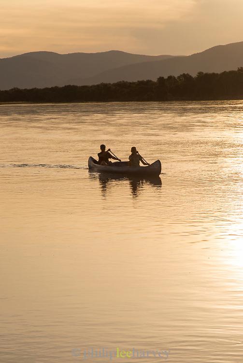 People in canoe paddling on river at sunset, Zambezi River, Zambia