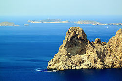 A small boat heading round Es Vedra island off the coast of Ibiza in the Balearic Islands.