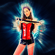 Digitally enhanced image of a Woman aged 30 in red and black latex holding a whip and a mouth gag, frontal view. Model Released
