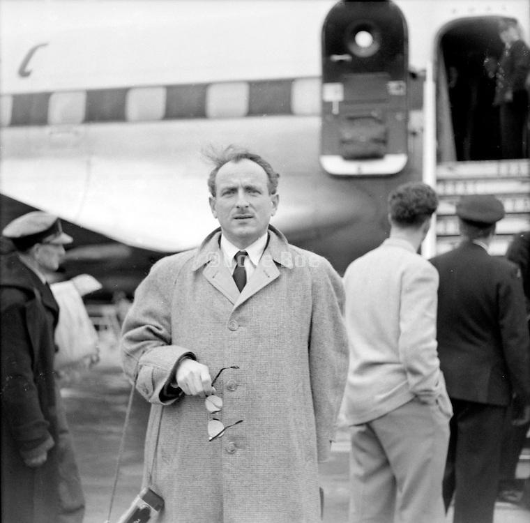 man posing before entering airplane 1950s