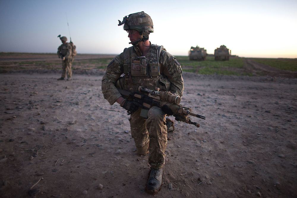 British soldiers of 16 Air Assault Bde's elite BRF (Brigade Reconnaissance Force) form a security cordon as fellow soldiers search a compound for weapons and explosives as part of an operation in the Western Dasht, Helmand Province, Southern Afghanistan on the 20th of March 2011.