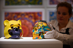 "© Licensed to London News Pictures. 14/09/2018. LONDON, UK. A technician inspects (L to R) ""Winnie The Pooh"", 2005, by Gary Hume (Est. GBP400-600) and ""The Hours Spin Skull"", 2009, by Damien Hirst (Est. GBP3,000-4,000) at a preview of the ""Yellow Ball: The Frank and Lorna Dunphy Collection"" sale at Sotheby's in New Bond Street.  Frank Dunphy was Damien Hirst's former business manager and mentor.  Over 200 works will be auctioned by Sotheby's on 20 September 2018.  Photo credit: Stephen Chung/LNP"