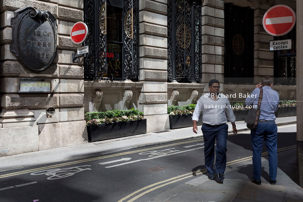 Two men pass each other on Finch Street, a narrow medieval-era lane in the City of London, the capital's historic financial district, on 2nd August 2018, in London, England.