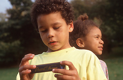 Brother and sister in park; boy holding mouth organ,