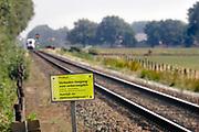 Nederland, Aalten, 28-8-2019Bij een met halve spoorbomen beveiligde spoorwegovergang in een lokale weg staat een waarschuwingsbord om niet voor de trein te springen .Foto: Flip Franssen