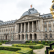 Part of the black and gold gate at right, with the Royal Palace of Brussels, the official palace of the Belgian royal family, in the main part of the frame.