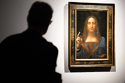 © Licensed to London News Pictures. 24/10/2017. London, UK. A visitor views a painting titled Salvator Mundi (1490) by artist Leonardo da Vinci with an estimate in excess of 00 million. The painting of Christ as Salvator Mundi was recently attributed to Leonardo da Vinci, who is known to have painted the subject. It was lost and later rediscovered, and restored and exhibited in 2011. Photo credit: Ray Tang/LNP