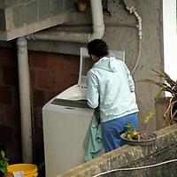 South America, Brazil. Rio de Janiero. Woman does laundry in favela of Rocinho.